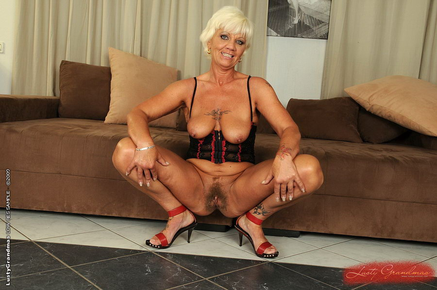 Home » Mature » Adel - Fit mature blonde with colorful tattoos pulls out  natural boobs from tight corset and squats down to show hairy pussy before  fucking ...